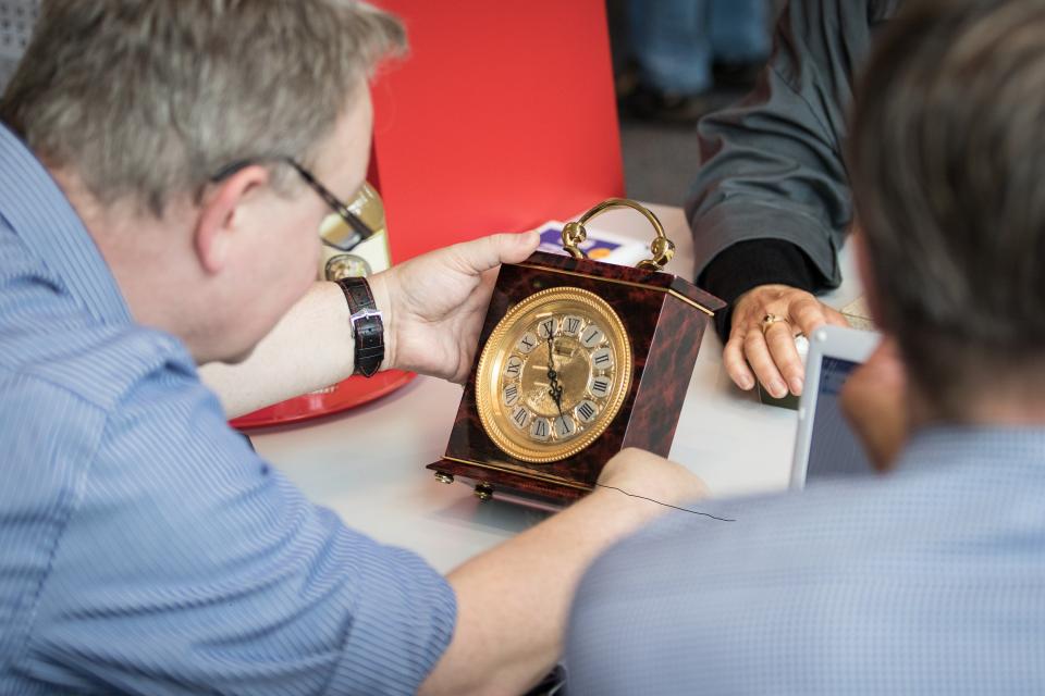 Bild: Mann schätzt den Wert einer Uhr